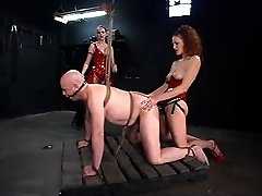 Two Dommes play with a rubber toy