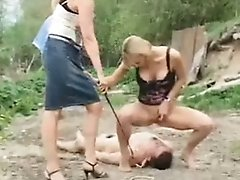 Horny femdom bitches take a naked leashed slave out for a walk at the dump and humiliate and torture him there