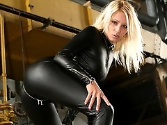 Natalie in black rubber catsuit tormenting chained slave