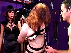 Asian domina and her male assistant prepare female slave for training in the dungeon
